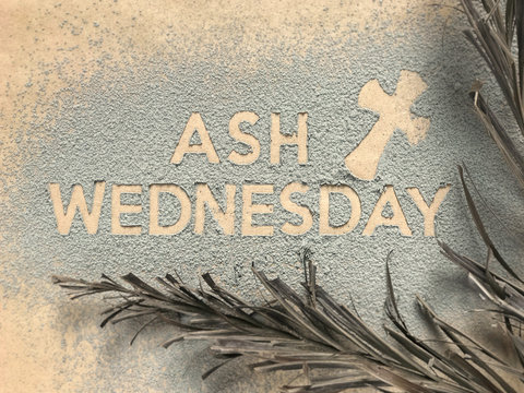 Ash Wednesday concept - Ash Wednesday words and a cross formed out of ashes. There are dry palm leaves on the sides.