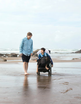 Father on beach with disabled son in wheelchair
