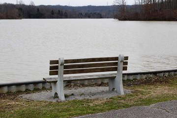 A empty wood park bench near the water of the lake.