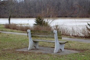 A empty wood park bench with a view of the lake.