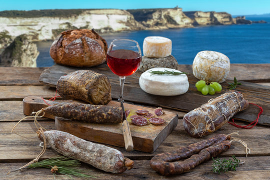 Corsican specialities: delicatessen, and cheese made in Corsica with the Porto veccio bay cliff panorama background, with a glass of wine