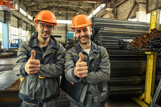 Cheerful industrial workers smiling showing thumbs up