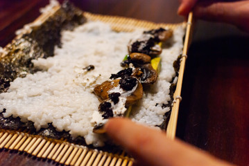 A young women rolling homemade vegan sushi on a wooden table
