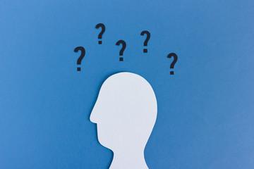 Viele Fragen: Kopf Silhouette aus Papier mit Fragezeichen