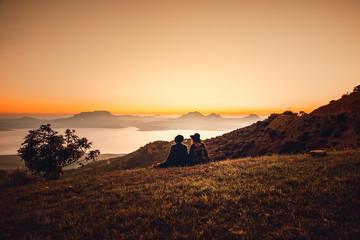 Ein Mann und eine Frau mit Poncho und Hut blicken auf das Rif Gebirge am El Wahda Stausee beim Sonnenuntergang in Marokko