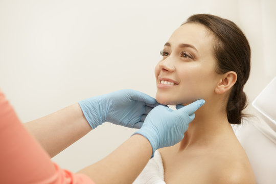 Young cheerful woman visiting her cosmetologist at the clinic