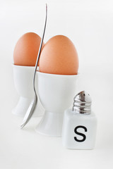 Two brown eggs with salt and salt shaker