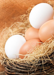 Brown and white eggs in wooden basket close up