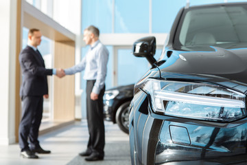 Professional salesman and his male customer at the car dealership showroom