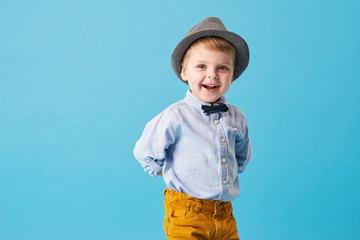 Portrait of happy joyful  little boy isolated on blue background. Toddler child in hat and fashionable suit smiling and have a fun  Wall mural