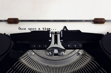Old retro vintage black typewriter with close-up typing text Once upon a time as heading on aged paper