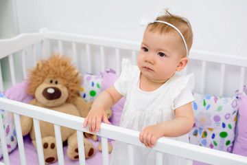 Portrait of 7 month old baby girl standing in white crib in light room