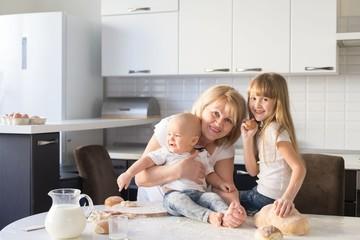 Grandmother, granddaughter and grandson, kitchen