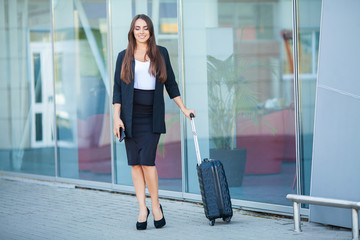 Young casual female goes at airport at window with suitcase waiting for plane