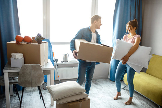 Young family couple bought or rented their first small apartment. They stand in room with box and pillows. People look at each other.