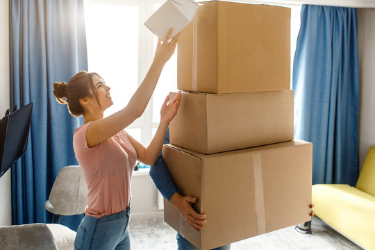 Young family couple bought or rented their first small apartment. Guy hold three cardboards. Young woman look up and reach box on top. Unpacking.