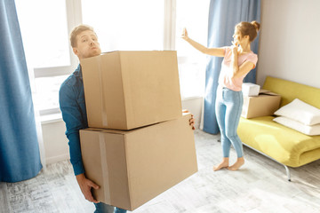 Young family couple bought or rented their first small apartment. Guy carry heavy boxes alone. Young woman stand at window and take selfie. Moving in. Unpacking.