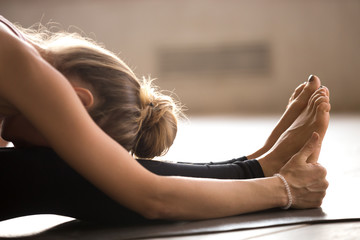Yogi young woman doing paschimottanasana exercise, close up