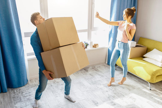 Young family couple bought or rented their first small apartment. Guy carry heavy boxes alone. Young woman take selfie at window and have fun. Unfair work. Moving and unpacking.