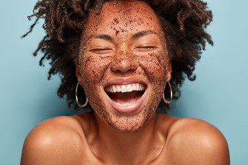 Overjoyed lady with peeling coffee scrub, laughs sincerely, has natural beauty, healthy dark skin, shows white teeth, bare shoulders, cleans face, isolated over blue background. Purity, cosmetology
