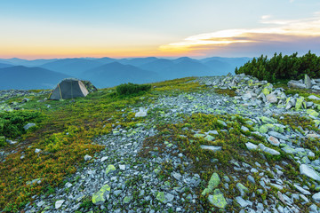 Journey through the mountain ranges and tops of the Ukrainian Carpathians, a tourist with a tent in a beautiful summer weather with fantastic sunrises and sunsets.