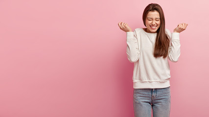 Joyful European woman raises hands with triumph, squints face, expresses happiness, wears casual jumper and jeans, celebrates victory, isolated over rosy background with empty space on left.