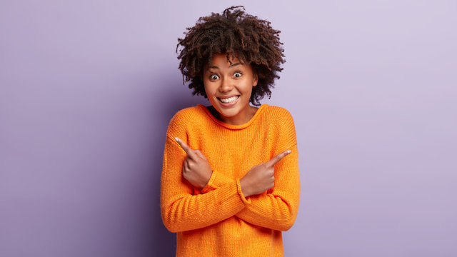 Indoor shot of cheerful woman points at different sides, feels enthusiasm and uncertainty, dressed in casual clothes, stands between choices, decides which deal to take, isolated over purple wall