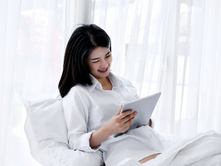 Asian woman sitting bed and play tablet, lifestyle concept