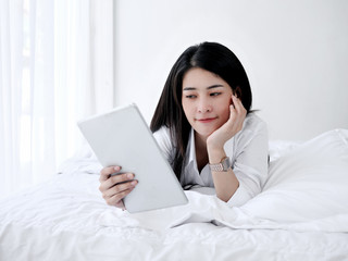 Asian woman laying on bed with tablet, lifestyle concept