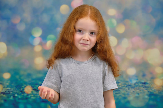 Concept portrait of a cute pretty child girl with red hair on a color background smiling and talking.