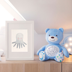 Stylish and cute nursery interior with mock up photo frame ,lighting cloud and blue teddy bear. White and sunny room with white background wall.
