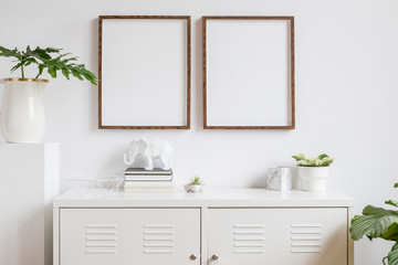 Stylish scandi home interior with two brown wooden mock up photo frames with books, beautiful plants in vase, elephant figure and home accessories. Minimalistic concept of white room decor.