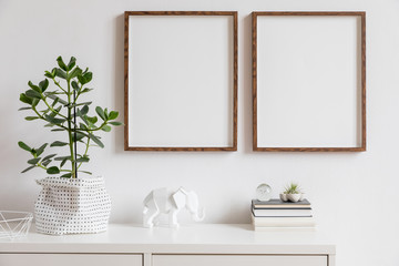 Stylish white home decor of interior with two brown wooden mock up photo frames with books, beautiful plant in stylish pot, elephant figure and home accessories. Minimalistic scandinavian room.