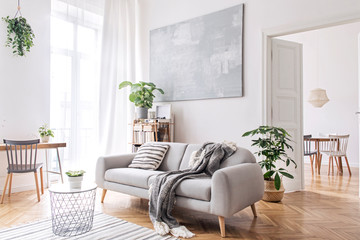 Fototapeta Modern scandianvian living room with design sofa with elegant blanket, coffee table and bookstand on the white wall. Brown wooden parquet. Concept of minimalistic interior.  obraz