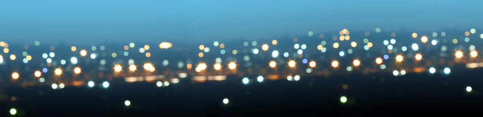Defocused or blurred image of multi-colored lights in the city streets. Abstract background, selective focus. Banner