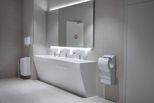 Hygiene, modern lifestyle and sanitary fixtures concept. Indoor shot of airport restroom with clean porcelain washstand, hand dryer and mirror on gray tiled wall with copyspace for your text