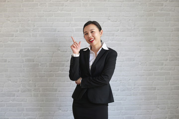 Young beautiful businesswoman smiling looking at camera pointing finger in side over white background.