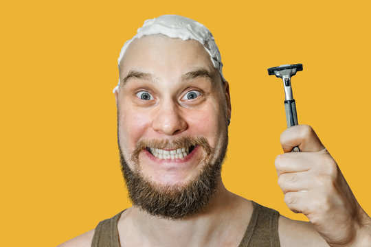 A guy with a beard and a razor in his hand, with foam and gel on his face shaves in the morning at home on a colored background