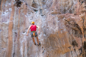 Men wearing red shirts are climbing high rocks,Extreme sports activities for the strength of the test,Concept: expedition aim for success and freedom lifestyle
