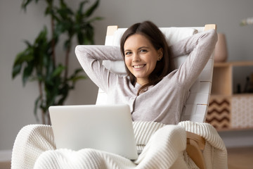 Head shot portrait of attractive woman using laptop, relaxing in chair