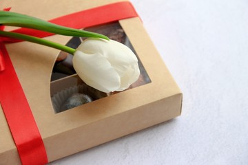 White tulip is on the box with sweets on a light background