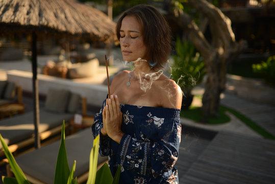 beautiful woman with brunette hair in dark swimwear and mirror glasses posing in blue pool in Bali