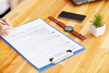 Contract. Blank of paper is on a wooden desk. Blank a4 paper is in the middle of wood office desk table with supplies. Top view with copy space, flat lay