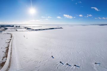 Winter coast, harbor and snow plain on the frozen sea at sunset