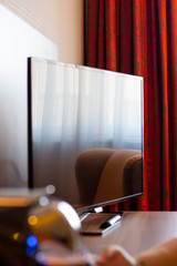 modern flat screen television in hotel room with red curtains