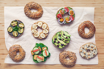 Stylish and tasty composition of vegan bagels sandwiches with vegetables, herbs, paste, seeds, hummus and lettuce on the brown wooden table. Fresh and healthy breakfast. Body balance. Lifestyle.