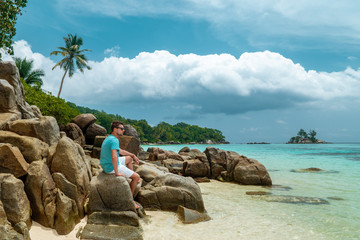 young men on tropical beach with palm tree, white beach man walking Seychelles Island, tanning men on tropical vacation