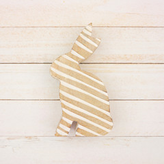 Wooden Easter bunny with white stripes against a rustic white wood background