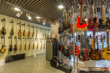Rows of acoustic guitars on the wall