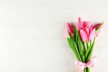 Fresh flower composition, bouquet of bi color pink tulips, white wooden texture table background. International Women's day, mother's day greeting concept. Copy space, close up, top view, flat lay.